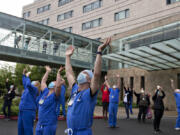 Amanda Cowan/The Columbian   Dr. Pierre Provost, an anesthesiologist at Legacy Salmon Creek Medical Center, joins colleagues and hospital staff as they greet members of the Oregon Air National Guard as they fly two F-15 Eagles over the area on Friday morning, May 22, 2020 as a tribute to front-line workers during the pandemic.