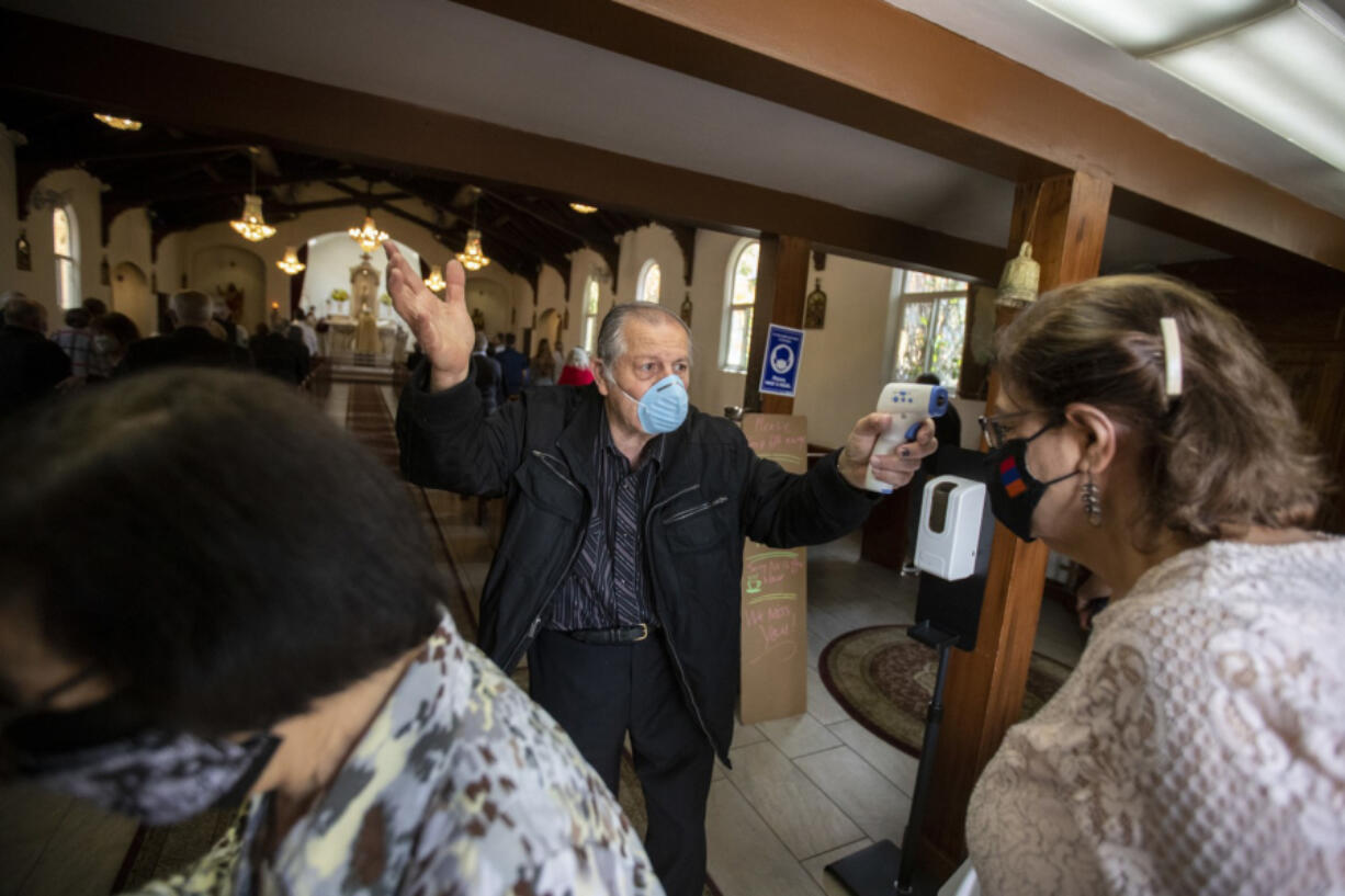 Usher Antoine Soumakian takes parishioners temperatures as they file in for Sunday service at Our Lady Queen of Martyrs Church, an Armenian church on Sunday, April 25, 2021 in Boyle Heights, CA.