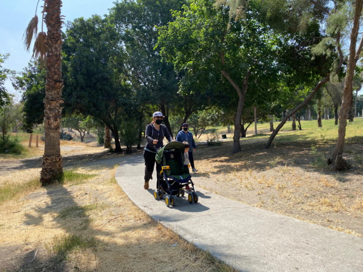 Tijuana resident Marcela Gonzalez, 44, pushes her son's stroller as he walks along side her on sunny morning in Parque Morelos on May 19, 2021.