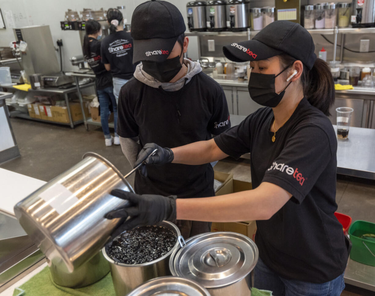 Sharetea owner NaNa Sisakvanich, right, combines vats of black tapioca pearls while Tyme Sisakvanich watches at Sharetea in Hazel Dell. A global shortage in the ingredients that make up the tapioca pearls in boba tea is affecting businesses that serve the colorful drinks.