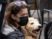 Vancouver resident Grace Wasser and poodle Archie pause at the Heathen Brewing Feral Public House in downtown Vancouver on Saturday during the Humane Society for Southwest Washington's fundraising event.