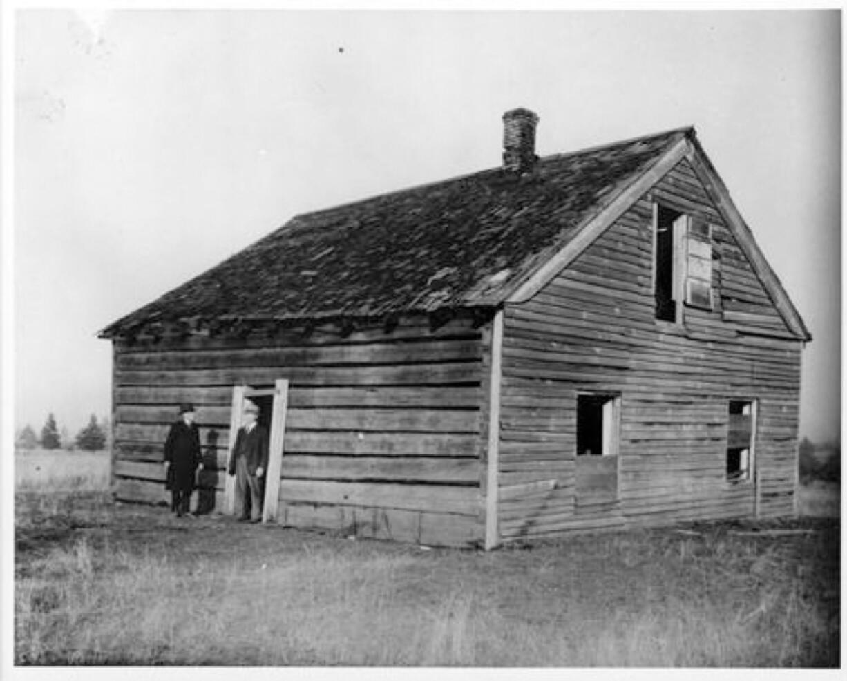 About 1920, two men in business-like dress stand near the doorway of the decaying Covington House at its original Orchards site on Covington Road. The Clark County Historical Society (then the Fort Vancouver Historical Society) and the Vancouver Women's Club planned on moving the cabin log by log in 1926 and rebuilt it about 1928 at today's location on Main Street near the Kiggins Bowl.
