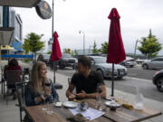 Seattle residents Becca Roundhill and Dominic Thibodeau enjoy red wine on an overcast April evening at Brian Carter Cellars at The Waterfront Vancouver. Getting a spot with a river view takes some planning.