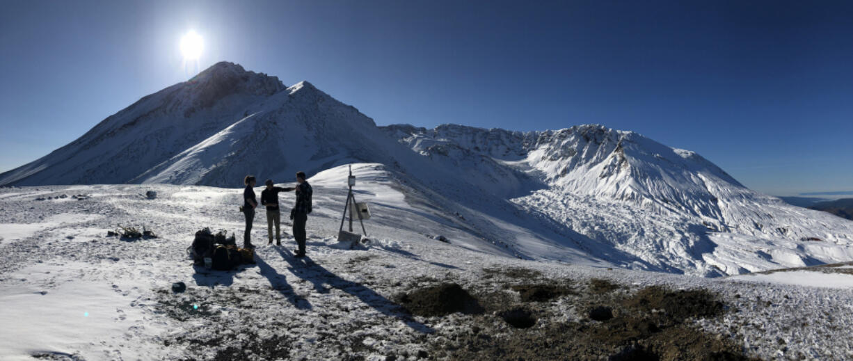 A field team from the Cascades Volcano Observatory discuss station maintenance plans on the north side of Mount St. Helens. Pictured in the center of the crater is a steaming lava dome from the 2004-08 eruption, and the fractured surface of Crater Glacier emerging from the gap on the north flank.