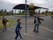 Kindergartners Makhari Lang, from left, Anthony Miller and Zephaniah Keli Aitu test their tetherball skills during recess at Eisenhower Elementary School on Monday. Vancouver Public Schools expanded in-person instruction for four grades and plans to expand to another four grades next week.