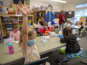 Kindergartner Emily Christel, foreground, joins classmates during in-person learning at Eisenhower Elementary School on Monday, the first day of expanded in-person instruction at Clark County's second-largest district.