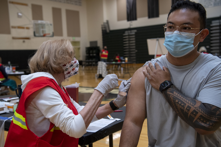 Medical Reserve Corps volunteer Ruth Gorley gives Vancouver resident Ryan Tydingco a Johnson & Johnson COVID-19 vaccine May 8 at Clark County Public Health's short-term vaccination pod at Woodland High School. After an early rush of people, the flow had slowed down by the late morning for the drop-in vaccination event.