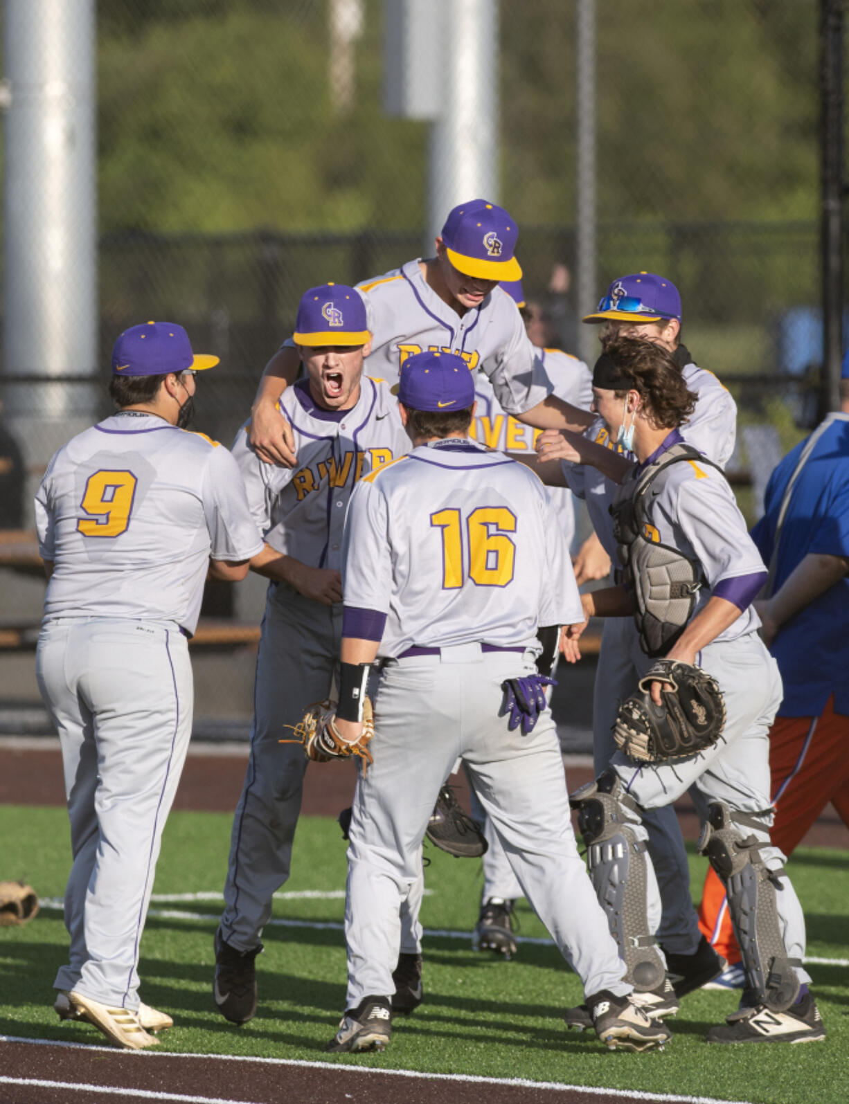 Columbia River players gather around pitcher Nick Alder, center, to celebrate a victory over Ridgefield on Tuesday, May 4, 2021, at the Ridgefield Outdoor Recreation Complex. Columbia River won 4-2 to advance in the 2A Southwest District Tournament.