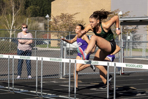 Woodland senior Lucy George clears a hurdle in the 100-meter hurdles at a 2A Greater St. Helens League track meet on  April 15 at Woodland High School. George, a Grand Canyon University track and field commit, hasn't lost an event this season - she has competed in the long jump, high jump, hurdles, javelin and shot put - and has a Division I collegiate spot locked up. But while others see athletic success, George struggles to find confidence in herself. She still battles with body image issues and grapples daily with overcoming an eating disorder that stemmed from a past coach telling her she needed to lose weight.