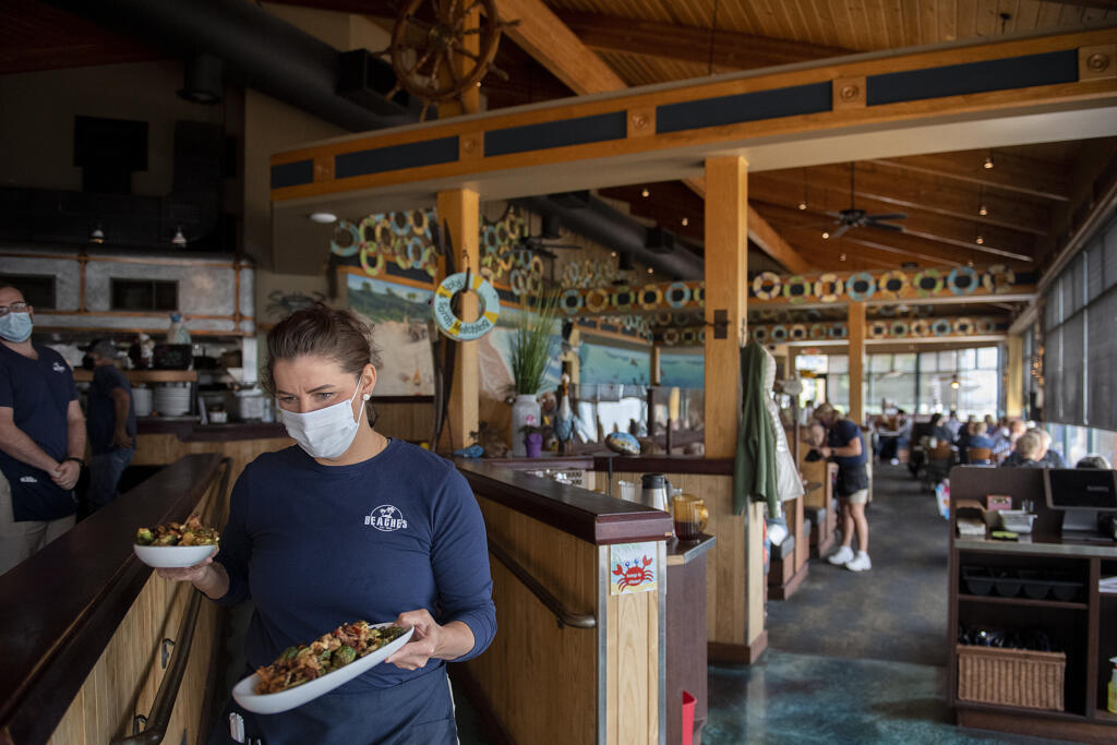Chrissy Gibbins of Beaches restaurant brings out dishes to lunchtime customers on Thursday morning, May 6, 2021. Beaches, along with most restaurants in Vancouver, is having trouble filling open positions.