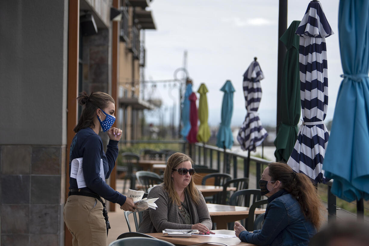 Mackenzie Samuelson, from left, of Beaches restaurant chats with customers Andrea Pelton and Maegan Davies while stopping by their table on Thursday morning, May 6, 2021.