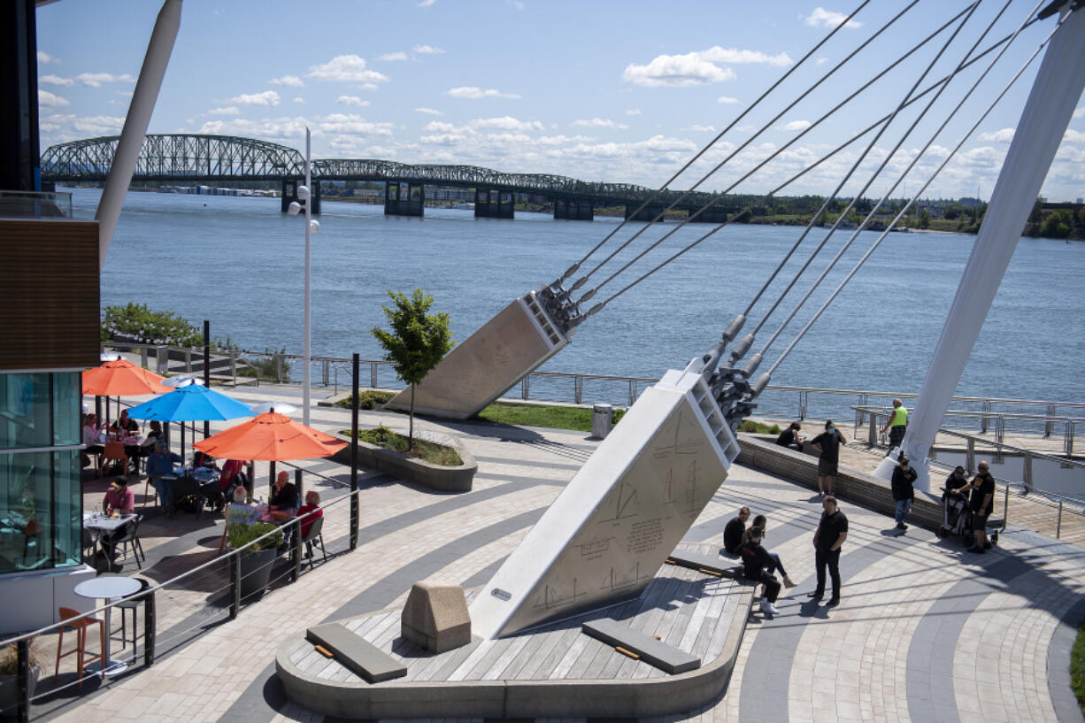 Visitors to The Waterfront Vancouver enjoy the sunny weather with a stroll or a lunch outside Tuesday afternoon. Clark County has fewer restrictions on activities than the rest of the Portland metro area, and local restaurants have seen an influx of customers from Oregon as a result.