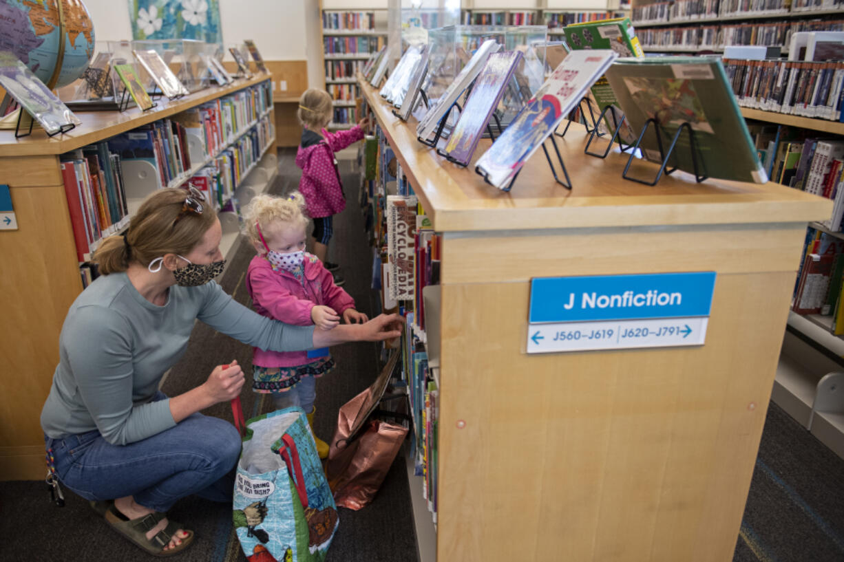Tami Widmer joins her daughters Dakota, 2, and Willow, 4, in picking out some fun children's books at Three Creeks Community Library on Monday morning. Monday was the first day the library was open for limited visits in person since March 2020.  At top, stuffed animals wear masks too as literary classics are displayed at the front of the library on Monday morning.