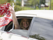 """In the back of a limo with a sparkling drink in hand, Kylie Dombrowsky celebrates receiving her bachelor's degree in business administration Saturday during the drive-through graduation ceremony for Washington State University Vancouver. """"If we're going to celebrate during COVID, we're going to celebrate right,"""" an elated Dombrowsky said."""