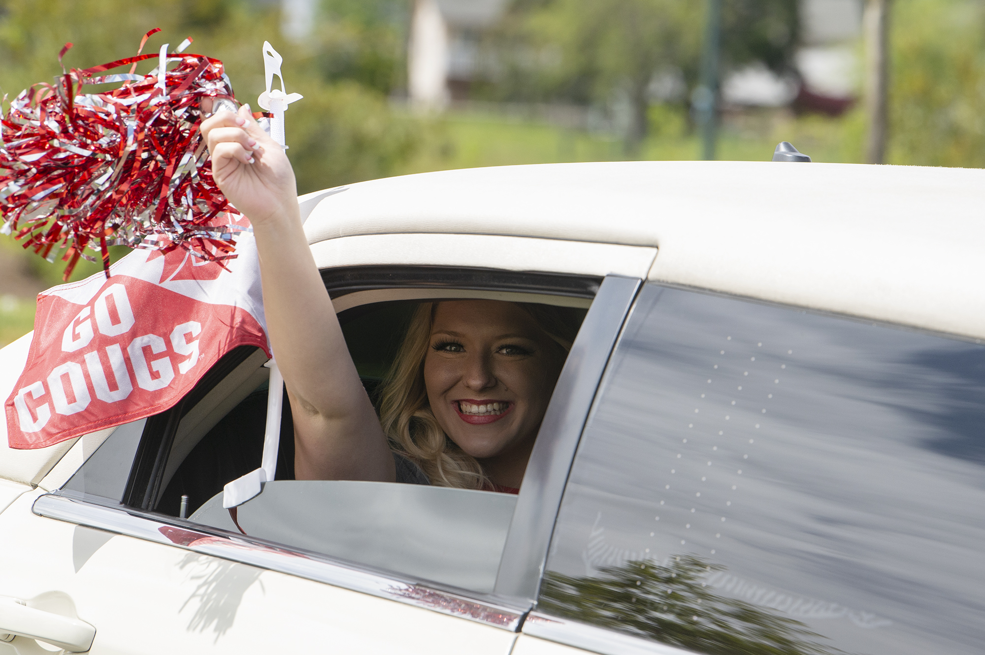 """In the back of a limo with a sparkling drink in hand, Kylie Dombrowsky celebrates receivering her diploma after graduating with a bachelor's degree in business administration at the drive-through graduation for Washington State University Vancouver on Saturday, May 8, 2021, in Vancouver. """"If we're going to celebrate during COVID, we're going to celebrate right,"""" an elated Dombrowsky said."""