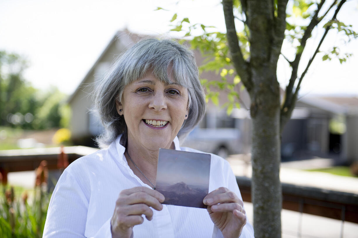 Jaquie Cole of Ridgefield pauses for a portrait with a photo she took of Mount St. Helens in 1980 on Monday afternoon, May 10, 2021. Cole and her friend flew in a small plane over Mount St. Helens on the afternoon of May 17, 1980, less than 24 hours before the big eruption.