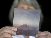 Jaquie Cole of Ridgefield displays a photo she took of Mount St. Helens in 1980 on Monday afternoon, May 10, 2021. Cole and her friend flew in a small plane over Mount St. Helens on the afternoon of May 17, 1980, less than 24 hours before the big eruption.