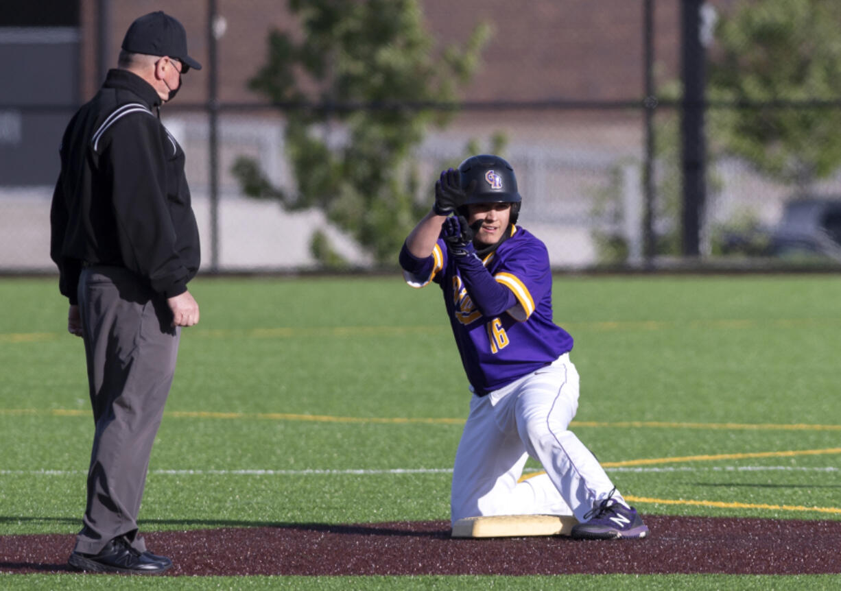 Columbia River's Jordan Wiggins claps toward his team'is dugout after a double in a 2A Southwest District Tournament third-place game on Friday, May 7, 2021, at the Ridgefield Outdoor Recreation Complex. Columbia River won 3-2 over Washougal in eight innings.