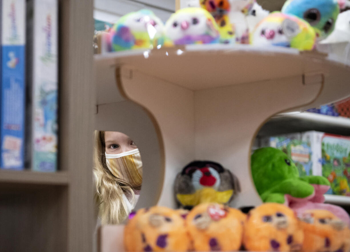Brooklyn Feustel looks through the selection at Kazoodles Toys in Vancouver. The toy store is one of many small businesses in Clark County that received Paycheck Protection Program loans last year. Local lenders have now turned to guiding their clients through the loan forgiveness process.