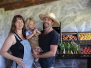 """MacKenzie Krumhauer, 28, son, Oliver, 1 1/2 , and her husband, Sean, enjoy their new home at Thiselle Creek Farm in Yacolt. The family moved from Southern California in 2018 due to a wildfire destroying their previous land.  """"""""We can learn from other mistakes to make it so we're working in symbiosis with the environment rather than pushing back,"""" MacKenzie said."""