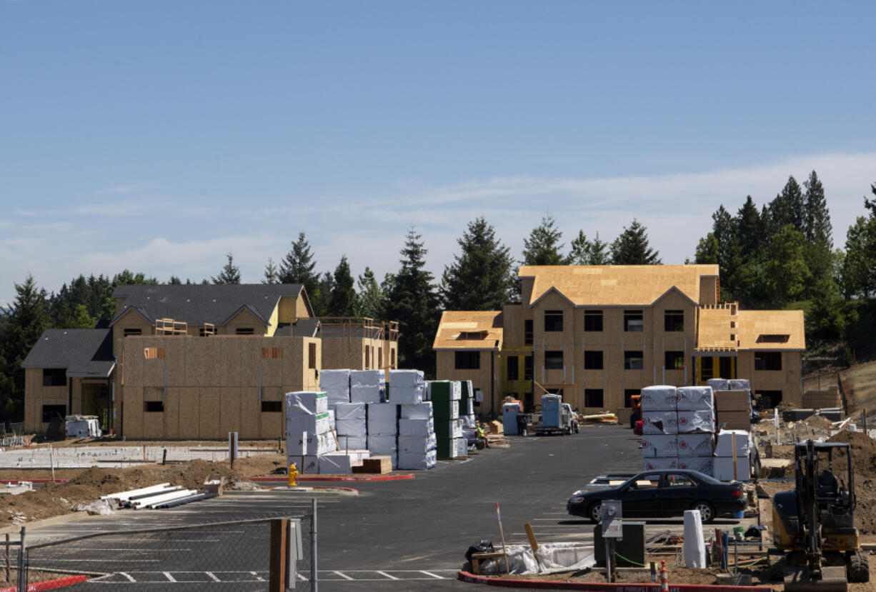 Stacks of lumber sit on the lot ready to be used to construct apartment buildings on Friday at the Latitude 45 apartment complex in Vancouver. Local builders have had to navigate rising lumber prices amid a national spike in demand.