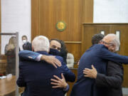 Attorney Evan Bariault. Facing from left, congratulates Don Benton as fellow attorney Mark Conrad supports Christopher Clifford after the jury ruled in their favor at the conclusion the lawsuit trial at the Clark County Courthouse on Thursday morning, May 20, 2021.