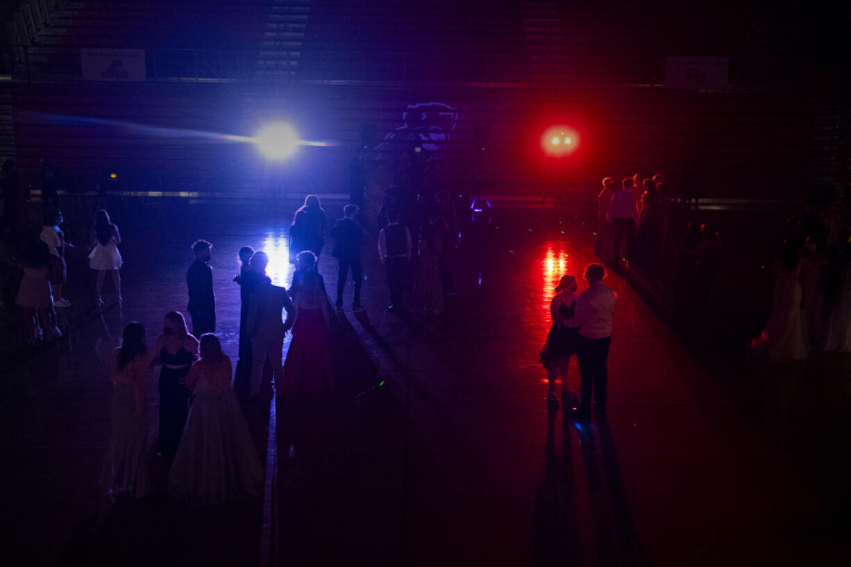 Colorful lights illuminate the gym at Fort Vancouver High School as students keep their distance while enjoying music, dancing and time with friends at the 2021 prom May 22. Some Clark County school districts did not permit traditional proms this spring for a second consecutive year because of COVID-19 safety restrictions. Others forged ahead this spring doing modified events or parent-driven pop-up proms not sponsored by schools.