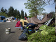 A worker removes garbage from a homeless encampment in northeast Vancouver on Thursday morning, April 29, 2021. Vancouver's new homeless resources coordinator is presenting her strategy for supported camp sites.