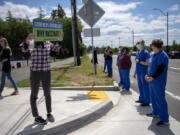 Protesters with opposite points of view on COVID-19 vaccination face off outside Ridgefield High School on Wednesday. Students at the high school helped organize a vaccination clinic in their school's gym.