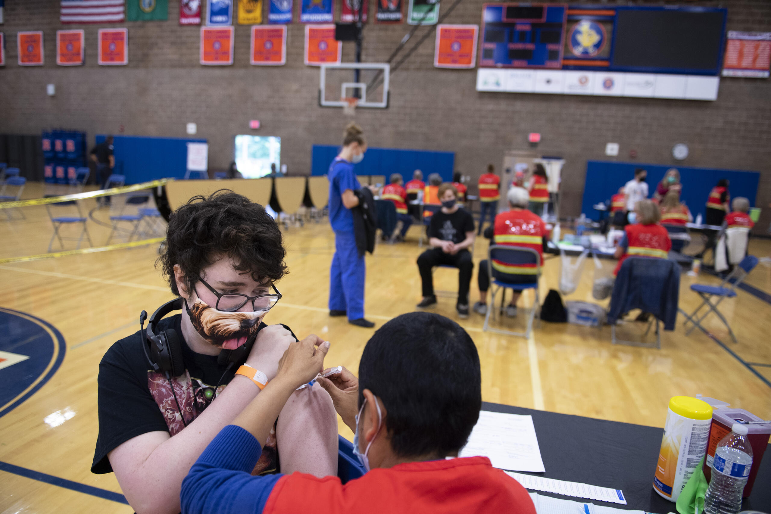 Ridgefield High School sophomore William Lewis, 16, left, wears a dog-themed mask as he receives his COVID-19 vaccination from pharmacist Estela Clemente in the school's gym on Wednesday morning, May 26, 2021. The vaccination clinic, which was also open to members of the community, was organized with help from students at the school.