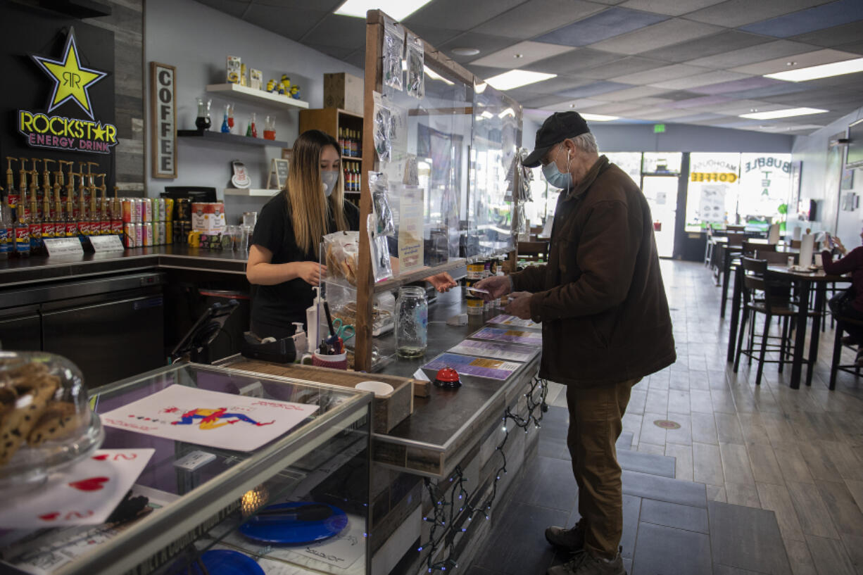Alisha Heilman serves customer Roger Keast of Vancouver on Friday morning at Madhouse Coffee in Vancouver.