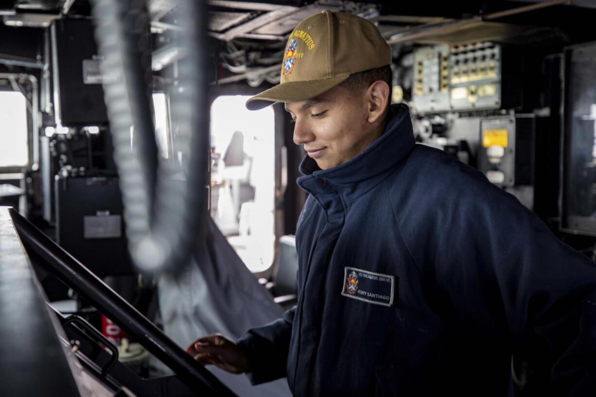 Seaman Kury Santiago, from Vancouver, mans the helm of the USS Paul Ignatius.