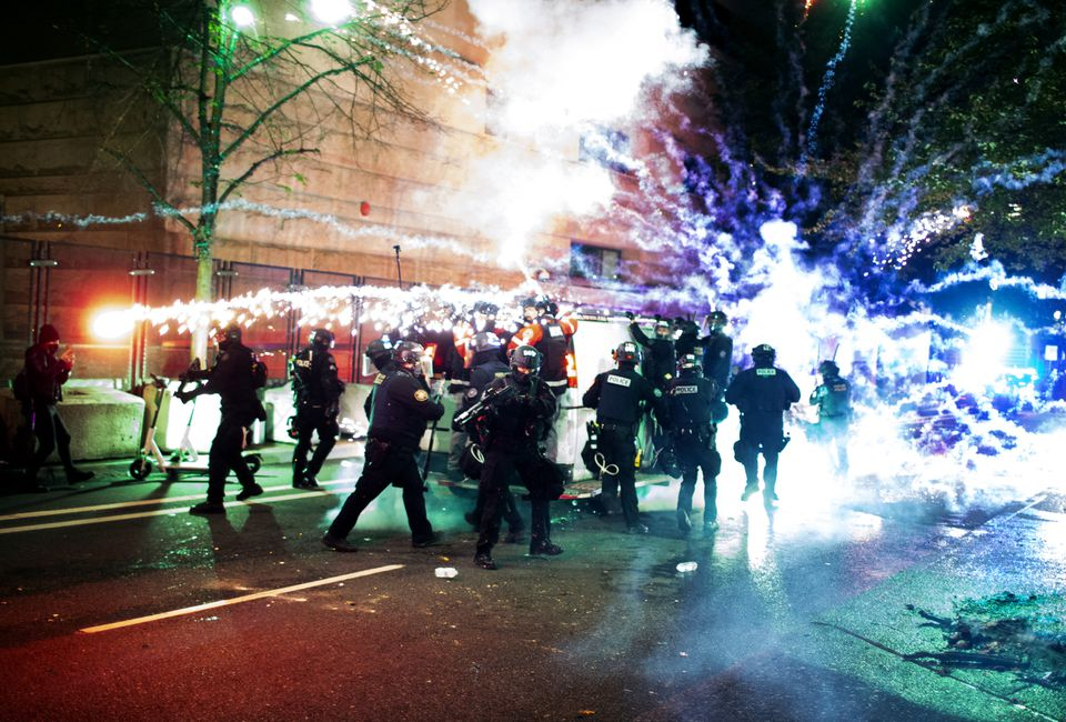 A firework thrown by protesters explodes near a group of police officers as they retreat after holding a line at an intersection.  A group of protesters gathered at the Justice Center in downtown Portland on May 25, 2021, to mark the passing of a year since a Minneapolis police officer murdered George Floyd.