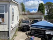 Clark-Cowlitz Fire Rescue crews make entry Tuesday afternoon into an attached garage on fire in Woodland. A small pet dog was found dead inside. The family was not home at the time of the blaze. The cause of the fire remains under investigation, according to the fire agency.