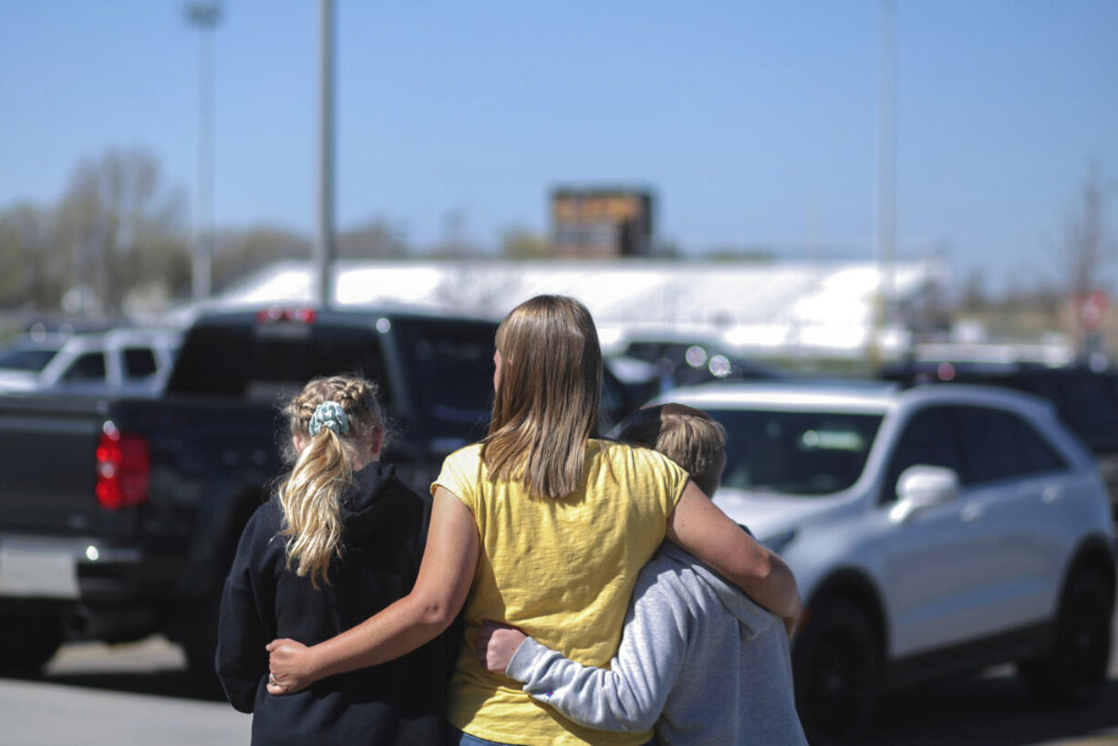 People embrace outside after a shooting at Rigby Middle School in Rigby, Idaho on Thursday, May 6, 2021.  Authorities say a shooting at the eastern Idaho middle school has injured two students and a custodian, and a male student has been taken into custody.