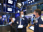 In this photo provided by the New York Stock Exchange, traders Gregory Rowe, center, and Robert Charmak, right, confer on the trading floor, Friday, May 7, 2021. Stocks are rallying to records on Wall Street Friday despite a stunningly disappointing report on the nation's job market, as investors see it helping to keep interest rates low.