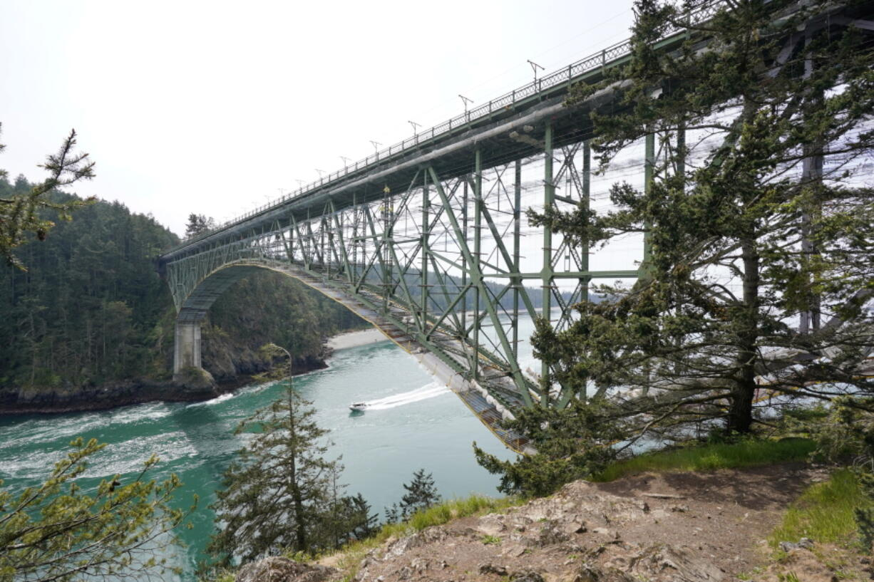 The Deception Pass Bridge, nearly 1,000-feet long and about 180-feet above the waters below, is covered in scaffolding as work to replace corroded steel and paint the structure continues Thursday, April 29, 2021, in Deception Pass, Wash. Raising state taxes to improve roads and bridges is one of the few things many Republican and Democratic lawmakers have agreed on in recent years. Those efforts have slowed to a crawl this year, even as lawmakers acknowledge a widening gap between needed work and the money to pay for it.