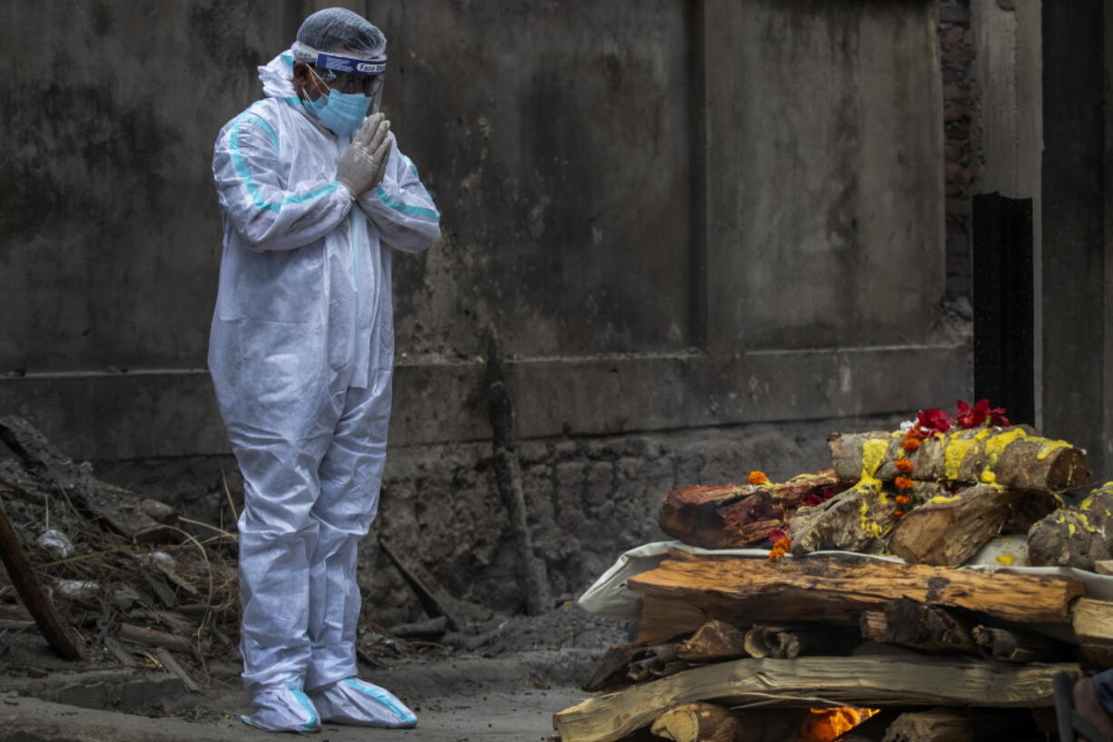 A relative in protective suit performs last rituals as the body of a person who died of COVID-19 is cremated in Gauhati, India, Monday, May 24, 2021. India crossed another grim milestone Monday of more than 300,000 people lost to the coronavirus as a devastating surge of infections appeared to be easing in big cities but was swamping the poorer countryside.
