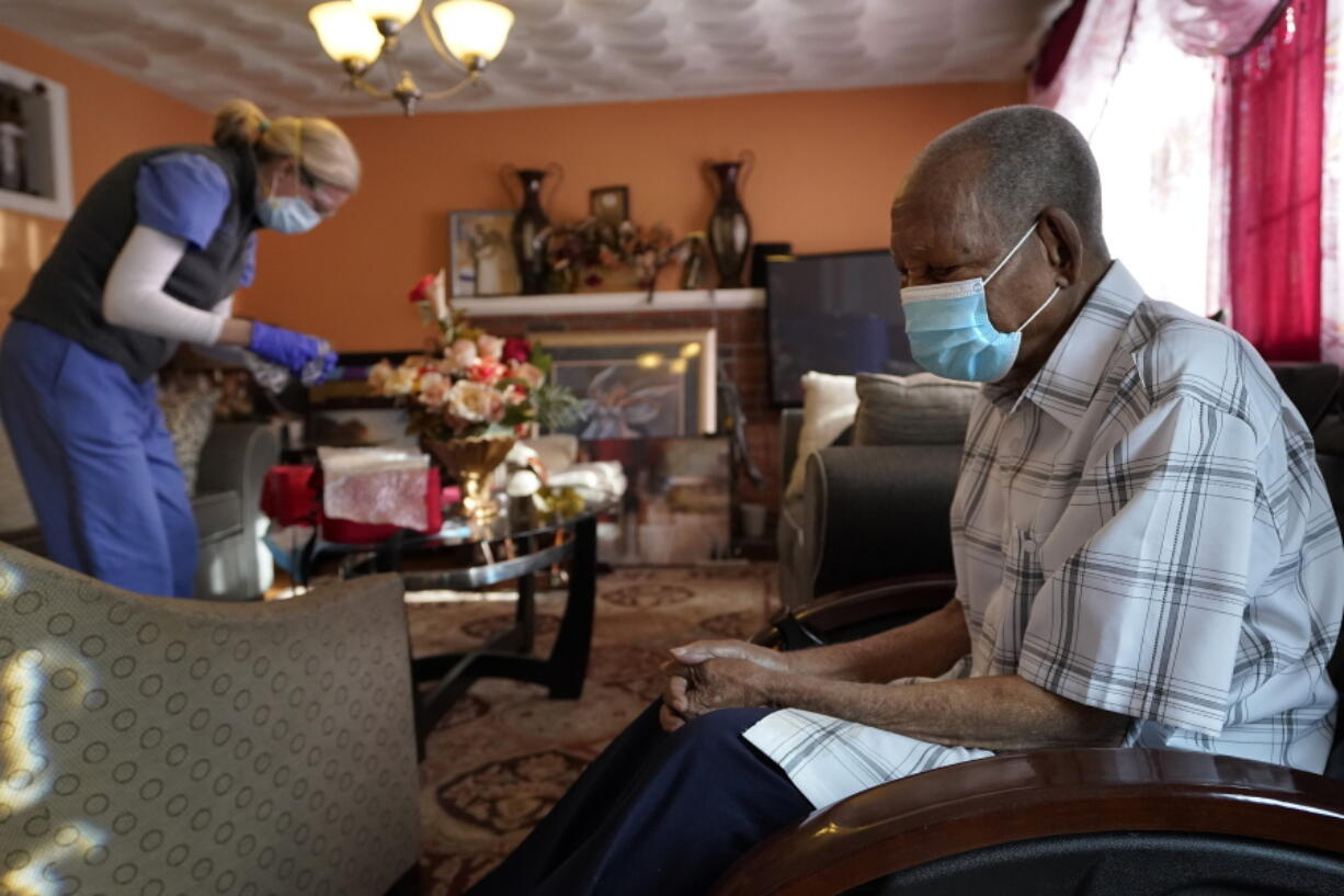 Edouard Joseph, 91, right, waits Feb. 11 as geriatrician Megan Young prepares to give him a COVID-19 vaccination at his home in the Mattapan neighborhood of Boston. A majority of Americans agree that government should help people age in their own homes, not institutional settings, according to a new survey from The Associated Press-NORC Center for Public Affairs Research.