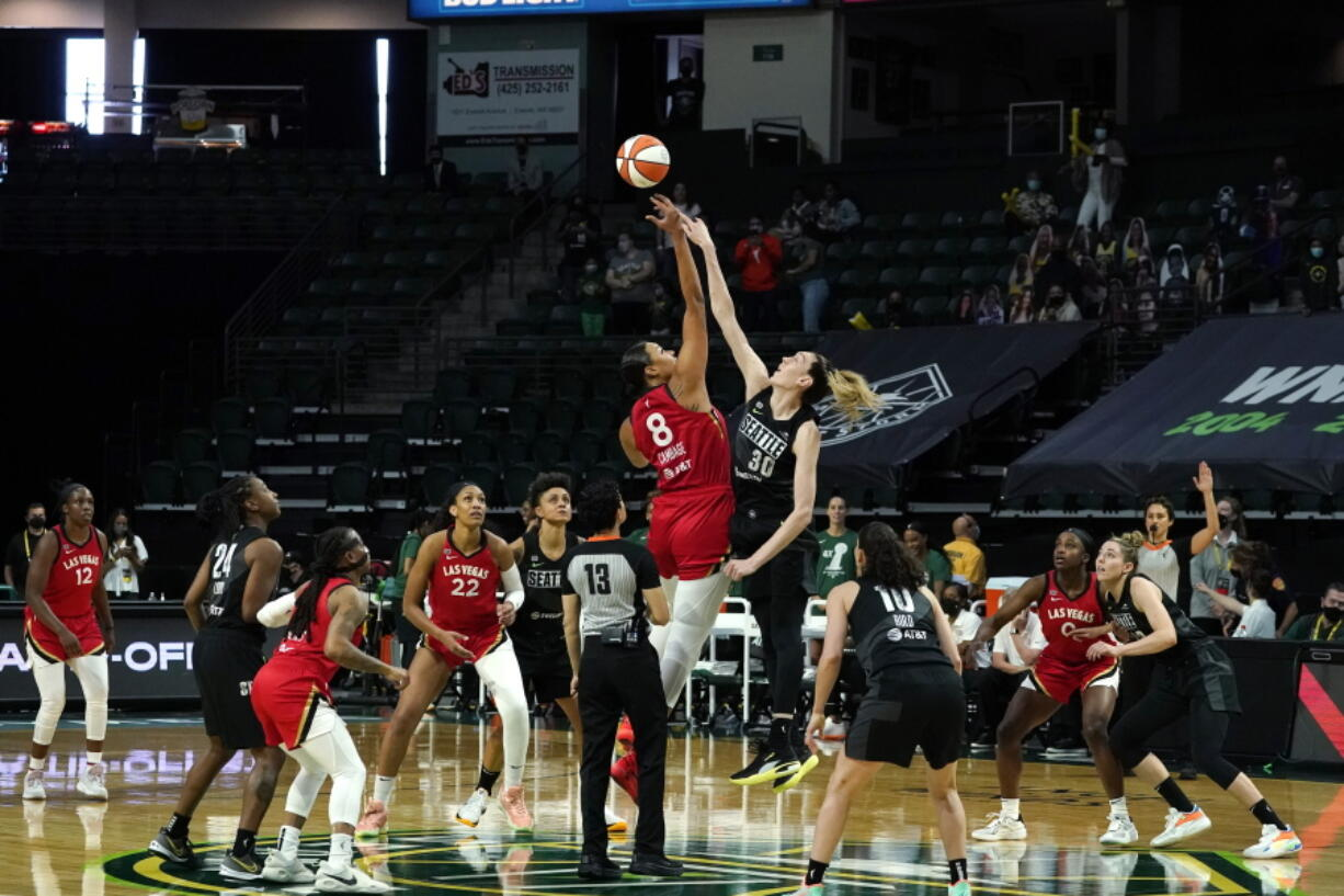 Las Vegas Aces' Liz Cambage (8) tips-off against Seattle Storm's Breanna Stewart to start the first half of a WNBA basketball game and their season Saturday, May 15, 2021, in Everett, Wash.