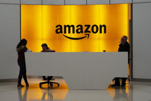 FILE - In this Feb. 14, 2019, file photo, people stand in the lobby for Amazon offices in New York. Amazon, which has been under pressure from shoppers, brands and lawmakers to crack down on counterfeits on its site, said Monday, May 10, 2021, that it blocked more than 10 billion suspected phony listings last year before any of their offerings could be sold.