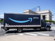 An Amazon truck drives in in Philadelphia, Friday, April 30, 2021.  Amazon is seeking to hire 75,000 people in a tight job market and is offering bonuses to attract workers, including $100 for new hires who are already vaccinated for COVID-19.