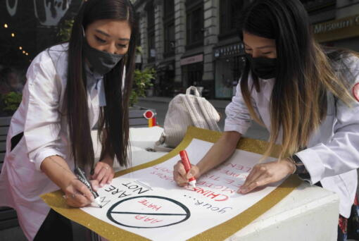 Dr. Michelle Lee, left, a radiology resident, and Ida Chen, right, a physician assistant student, prepare posters they carry at rallies protesting anti-Asian hate, Saturday April 24, 2021, in New York's Chinatown. Lee, who is Korean-born, and Chen, who is American-born Chinese, join medical professionals of Asian and Pacific Island descent who feel the anguish of being racially targeted because of the virus while toiling to keep people from dying of it.