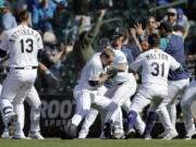 Seattle Mariners players surround Tom Murphy, center, after he hit a sacrifice fly, scoring the winning run, in the 10th inning against the Oakland Athletics on Monday in Seattle. The Mariners won their fifth straight game and improved to 5-0 in extra innings.