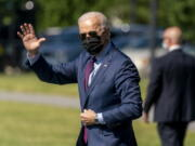 President Joe Biden waves as he walks towards Marine One on the Ellipse at the White House in Washington, Tuesday, May 18, 2021, for a short trip to Andrews Air Force Base, Md., and then on to Detroit to visit the Ford Rouge Electric Vehicle Center in Dearborn, Mich.