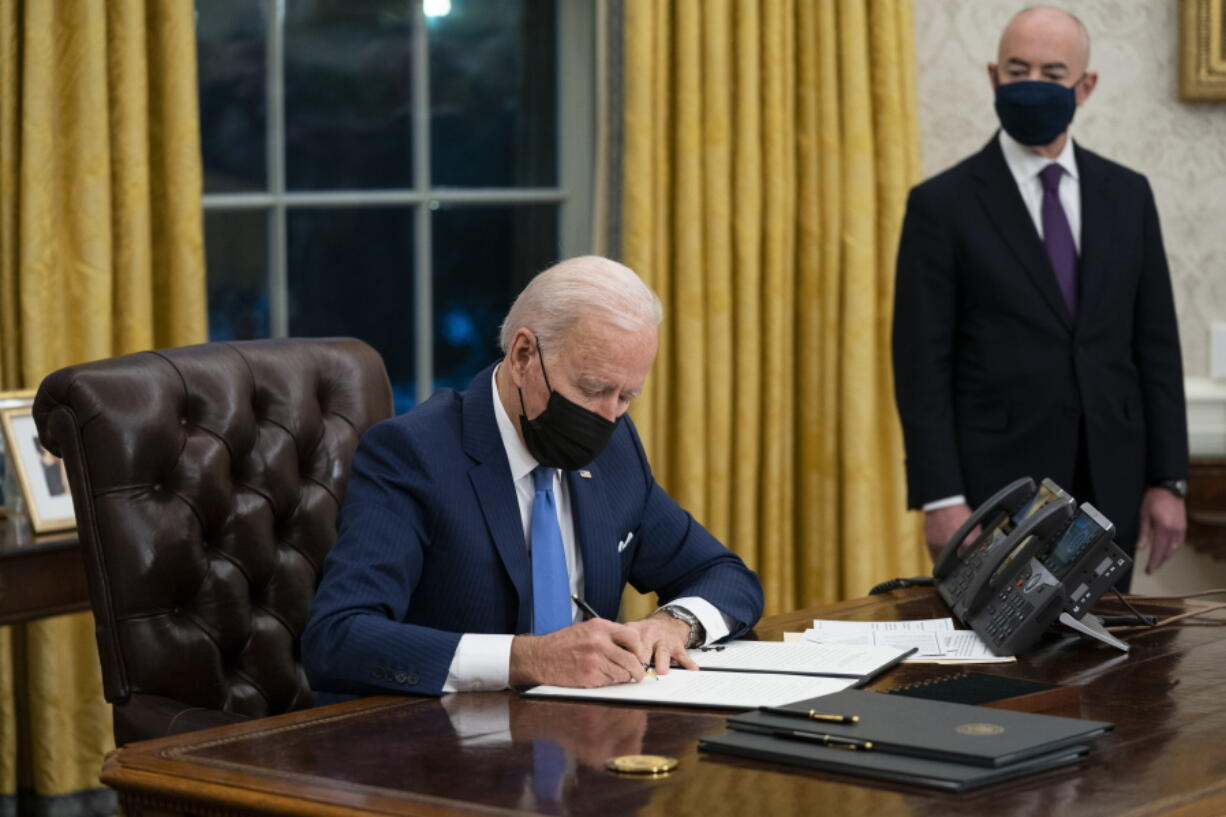FILE - In this Tuesday, Feb. 2, 2021, file photo, Secretary of Homeland Security Alejandro Mayorkas looks on as President Joe Biden signs an executive order on immigration, in the Oval Office of the White House in Washington. Biden, under political pressure, agreed to admit four times as many refugees this budget year as his predecessor did, but resettlement agencies concede the number actually allowed into the U.S. will be closer to the record-low cap of 15,000 set by former President Donald Trump.