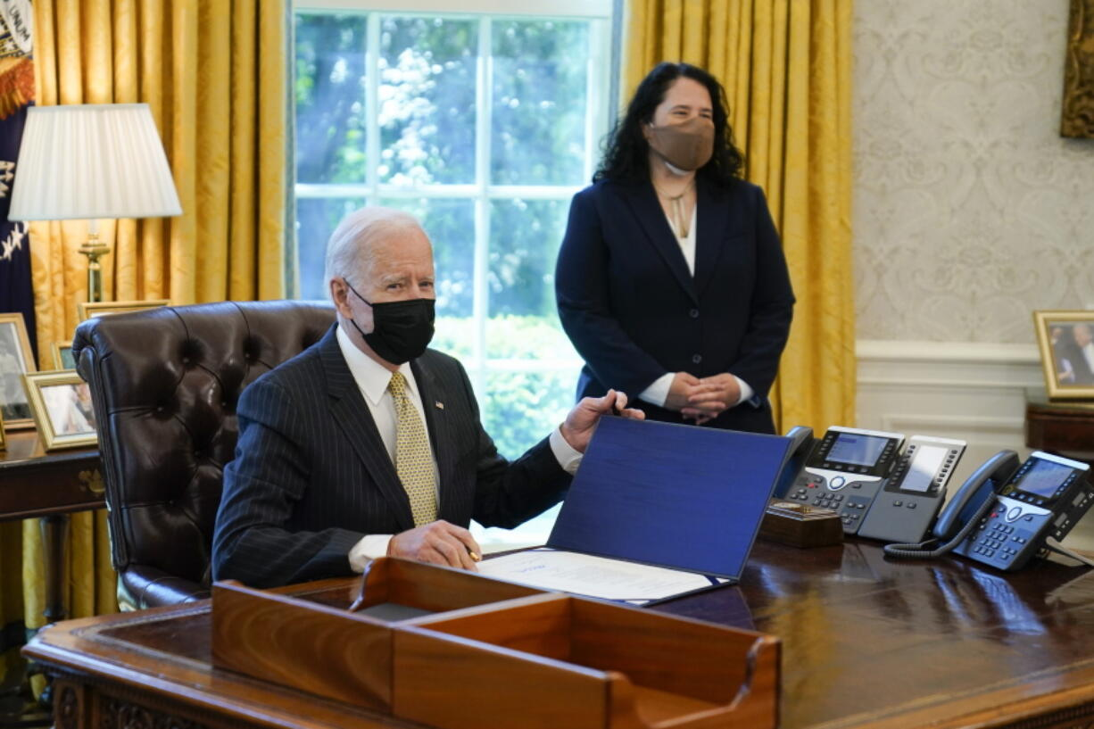 In this March 30, 2021 photo, President Joe Biden signs the PPP Extension Act of 2021, in the Oval Office of the White House in Washington. Small Business Administration administrator Isabel Guzman is at right. Biden is promoting his $28.6 billion program to help the restaurants, bars and food trucks hurt by the coronavirus pandemic.