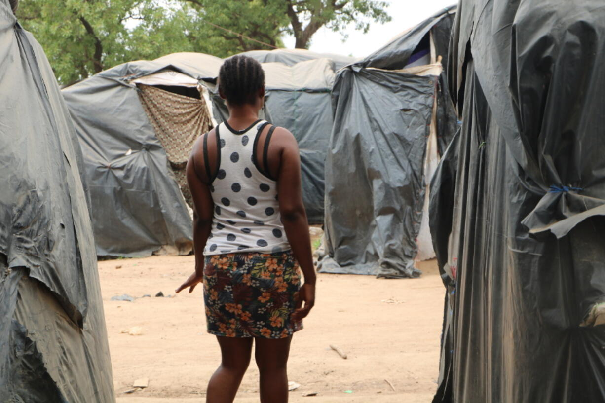 A woman who said she was trafficked from Nigeria under false pretenses to work as a sex slave in Burkina Faso's mining sites, walks through a row of tent in the Secaco mining town June 12, 2020. As part of a months-long investigation into sex trafficking and the gold mining industry, The Associated Press met with nearly 20 Nigerian women who said they had been brought to Burkina Faso under false pretenses, then forced into prostitution.