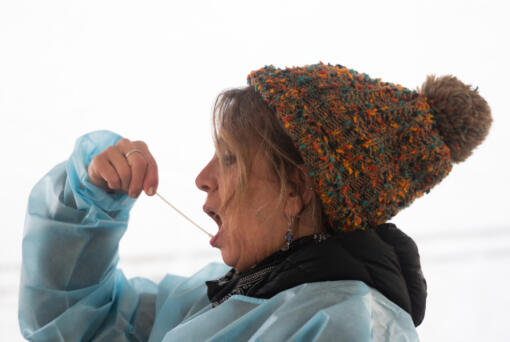 Kelly Lund swabs her mouth while demonstrating a self-administered oral COVID-19 test at the Tower Mall parking lot in January. The county closed that testing site on April 30 to focus on giving more COVID-19 vaccines at the site.
