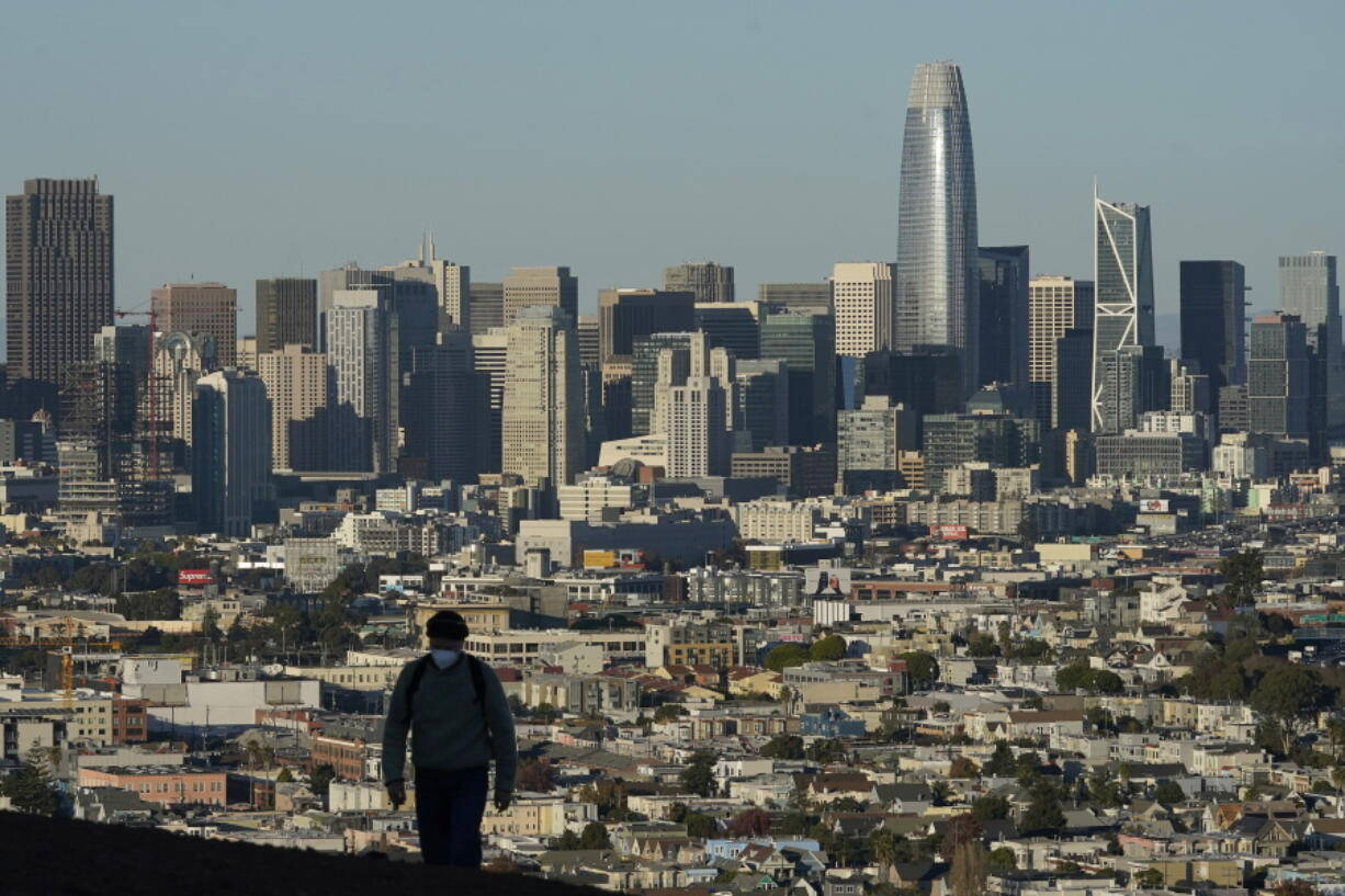 FILE - In this Dec. 7, 2020, file photo, a person wearing a protective mask walks in front of the skyline on Bernal Heights Hill during the coronavirus pandemic in San Francisco. California's population has declined for the first time in its history. State officials announced Friday, May 7, 2021, that the nation's most populous state lost 182,083 people in 2020. California's population is now just under 39.5 million.